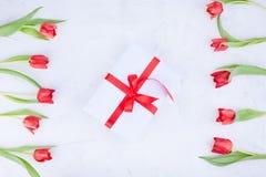 Bukiet czerwoni tulipany i pude?ko z ??kiem na bia?ym tle Niespodzianka i kwiaty dla romantycznego wakacje Prezent dla mamy lub zdjęcie royalty free