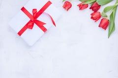Bukiet czerwoni tulipany i pude?ko z ??kiem na bia?ym tle Niespodzianka i kwiaty dla romantycznego wakacje Prezent dla mamy lub zdjęcia royalty free