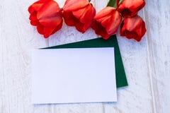 Bukiet czerwoni tulipany na tle bia?e deski miejsce tekst Poj?cie wiosna przychodzi? fotografia stock
