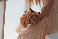 Bukiet delikatne menchii kiści róże na tle menchii koronka ubiera, dziewczyny ręka Zdjęcie Stock