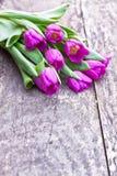 Bukiet fiołkowi tulipany na dębowym brązu stole Fotografia Royalty Free