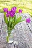 Bukiet fiołkowi tulipany na dębowym brązu stole w jasnym szklanym słoju Fotografia Stock