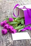Bukiet fiołkowi tulipany pakuje a na dębowym brązu stole Zdjęcia Stock