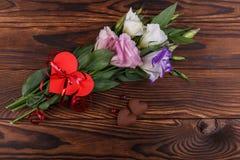 Bukiet Japońskie róże wiązał z faborkiem z sercem na drewnianym tle na widok zdjęcie royalty free