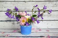 Bukiet kwiatów dzwony i dzikie róże w szklanej wazie Zdjęcie Stock