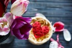 Bukiet kwiatów tulipany i czerwony drewniany serce kłama w pudełku na zmroku stole z menchiami, fiołkowi płatki wokoło zdjęcie royalty free