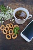 Bukiet kwiaty i filiżanka herbata na drewnianym stole z telefonem z pustym ekranem Obraz Stock