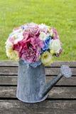 Bukiet kwiaty w srebnej podlewanie puszce Obrazy Stock