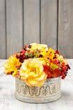 Bukiet pomarańczowe róże i jesieni rośliny w rocznika ceramicznym vas Fotografia Stock