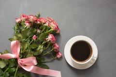 Bukiet różowe róże i filiżanka kawy na szarym tle Odgórny widok Romantyczna karta z miłością Zdjęcie Stock