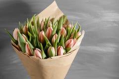 Bukiet różowi tulipany w pakunku Kraft papier na szarość, wodden tło Obrazy Royalty Free