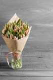 Bukiet różowi tulipany w pakunku Kraft papier na szarość, wodden tło Obrazy Stock