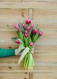 Bukiet tulipany w ręce na drewnianym tle Obrazy Stock
