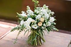 bukieta ręki panny młodej fornala ręki Panny młodej ` s Piękny biali kwiaty i greenery, dekorujący z jedwabniczym faborkiem, kłam fotografia stock
