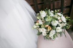 bukieta ręki panny młodej fornala ręki Panny młodej ` s Piękny biali kwiaty i greenery, dekorujący z jedwabniczym faborkiem, kłam obraz stock