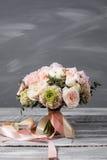 bukieta ręki panny młodej fornala ręki _ Piękny bukiet biel, menchia kwiaty i greenery, dekorował z długim jedwabniczym faborkiem Fotografia Royalty Free