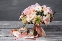 bukieta ręki panny młodej fornala ręki _ Piękny bukiet biel, menchia kwiaty i greenery, dekorował z długim jedwabniczym faborkiem Zdjęcia Royalty Free