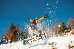 Bukovel,乌克兰- 2016年12月22日:供以人员跳跃在他的雪板的房客反对山,小山背景和 库存图片