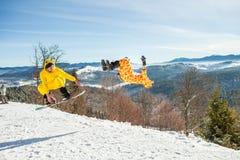 Bukovel,乌克兰- 2016年12月22日:跳跃在他的雪板的人房客反对山,小山背景和 免版税库存图片