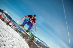 Bukovel, Ucrânia - 22 de dezembro de 2016: Equipe o pensionista que salta em seu snowboard contra o contexto das montanhas, monte Imagens de Stock