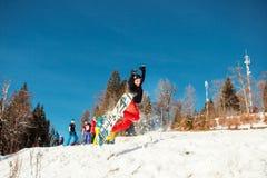 Bukovel, Ucrânia - 22 de dezembro de 2016: Equipe o pensionista que salta em seu snowboard contra o contexto das montanhas, monte Fotos de Stock Royalty Free