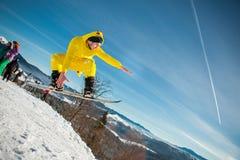 Bukovel, Ucrânia - 22 de dezembro de 2016: Equipe o pensionista que salta em seu snowboard contra o contexto das montanhas, monte Imagens de Stock Royalty Free