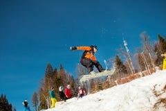 Bukovel, Ucrânia - 22 de dezembro de 2016: Equipe o pensionista que salta em seu snowboard contra o contexto das montanhas, monte Imagem de Stock Royalty Free