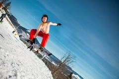 Bukovel, Ucrânia - 22 de dezembro de 2016: Equipe o pensionista que salta em seu snowboard contra o contexto das montanhas, monte Fotos de Stock