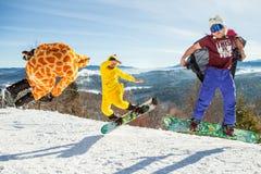 Bukovel, Ucrânia - 22 de dezembro de 2016: Pensionistas dos homens que saltam em seu snowboard contra o contexto das montanhas, m Imagem de Stock