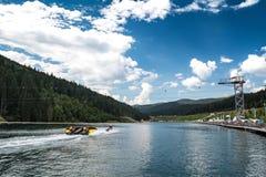 Bukovel, Ucraina - 21 agosto 2018: Lago della gioventù Attrazioni sulla spiaggia Bici dello zip, torre dell'adrenalina, bungee ju immagine stock libera da diritti