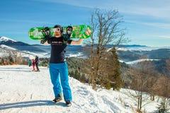 Bukovel Ukraina, Grudzień, - 22, 2016: Obsługuje trzymać jego snowboard przeciw tłu góry, wzgórza i lasy, wewnątrz Obrazy Stock