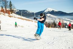 Bukovel, Ukraine - December 22, 2016: Man boarder jumping on his snowboard against the backdrop of mountains, hills and Stock Photos