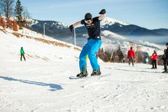Bukovel, Ukraine - December 22, 2016: Man boarder jumping on his snowboard against the backdrop of mountains, hills and. Forests in the distance at Bukovel Royalty Free Stock Photo