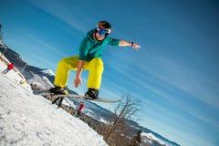 Bukovel, Ukraine - 22. Dezember 2016: Bemannen Sie den Internatsschüler, der auf seinen Snowboard gegen den Hintergrund von Berge Lizenzfreie Stockfotos