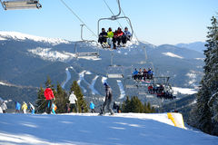 BUKOVEL, UKRAINE - FEBRUARY 17: The cableway and skiers on slope Stock Photos