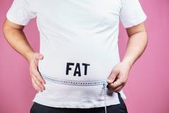 Bukta fett, frossare Fet man med måttbandet arkivfoto