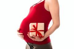 Bukta gravida kvinnan i röd t-skjorta med en gåva i händerna Royaltyfri Bild