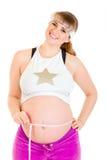 bukta henne den mätande gravida le kvinnan Arkivfoto