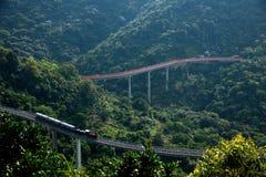 Buktade förlängningen för den OKTOBER utbildar den östliga Shenzhen Meisha teströmmen dalen av skogarna i bergen järnvägen Arkivfoton
