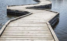 Buktigt sväva går vägen över vatten Arkivfoto