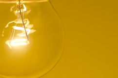 Bulb. Close up of light bulb against orange background - shallow depth of field Royalty Free Stock Image