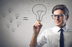 Bulb. Handsome businessman with glasses drawing a bulb Stock Images