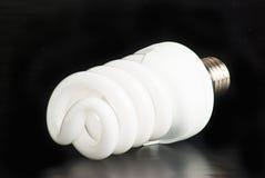 Bulb. Electric energy saving bulb on a black background Stock Photography