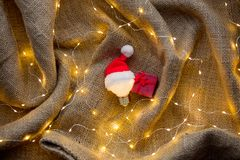 Bulb in Christmas hat and gfit box. On jute background Stock Photos