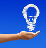 Bulb from clouds. In hands on blue sky Royalty Free Stock Photos