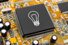 Bulb on computer chip Stock Images