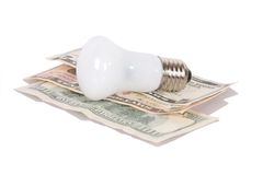 Bulb on dollars Royalty Free Stock Image