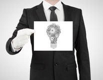 Bulb in form gears and cogs. Businessman in suit holding placard with bulb in form gears and cogs Stock Images