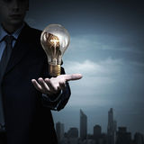 Bulb in hand. Businessman presenting glass glowing light bulb in his hand Stock Images