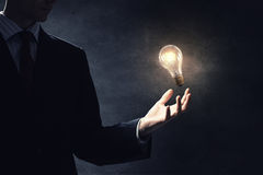 Bulb in hand Stock Images